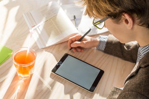 Studente maschio in giacca di tweed che fa i compiti al caffè durante l'ora di pranzo