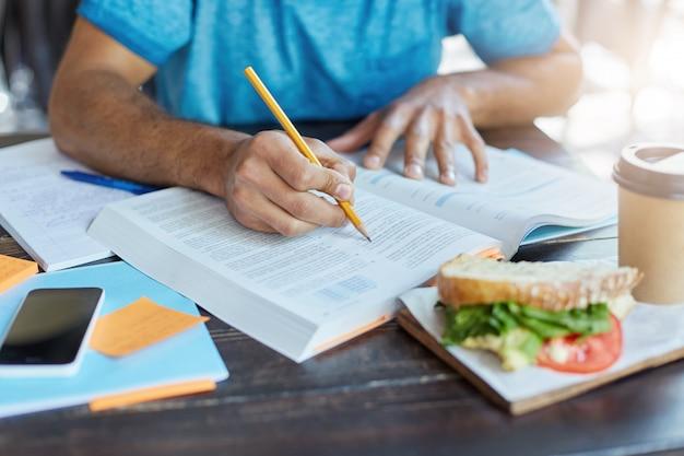 Studente maschio nero che sottolinea informazioni importanti nel libro di testo usando la matita mentre fa ricerche storiche alla mensa universitaria durante il pranzo; telefono, caffè e cibo appoggiati sul tavolo