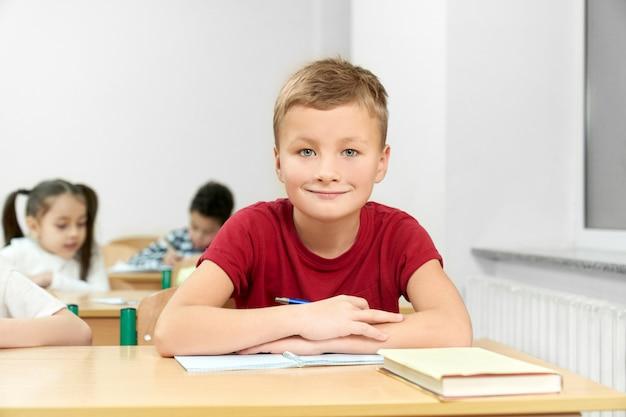 Studente maschio seduto alla scrivania con le braccia conserte durante la lezione