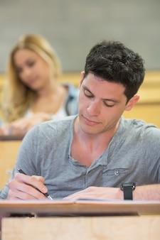 Studente maschio serio durante la lezione in aula