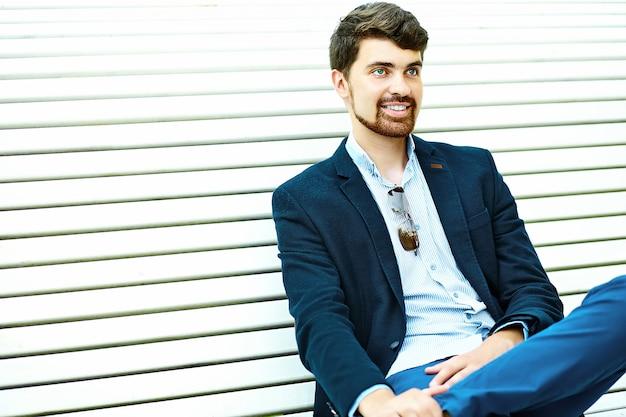 Studente maschio sorridente bello giovane dei pantaloni a vita bassa che si siede sul banco in un parco in vestito