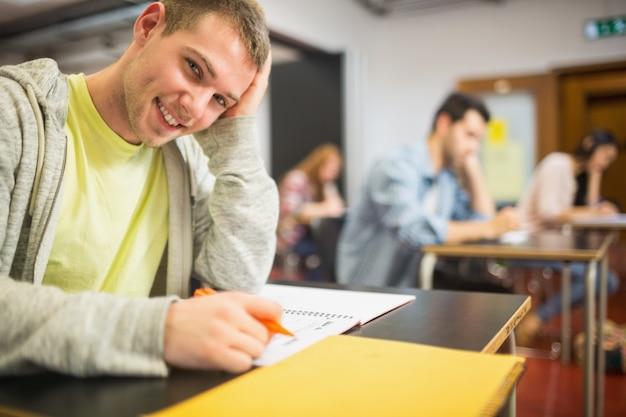 Studente maschio sorridente con altri che scrive le note in aula