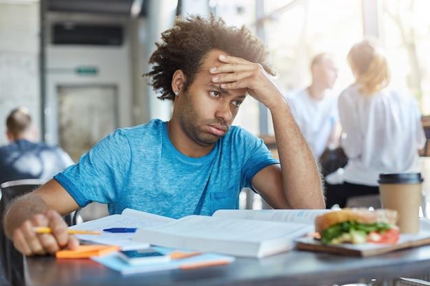 Studente maschio stressato frustrato seduto al tavolino del bar con libri, appunti e pranzo, con uno sguardo stanco esausto mentre non riesce a risolvere il problema matematico.