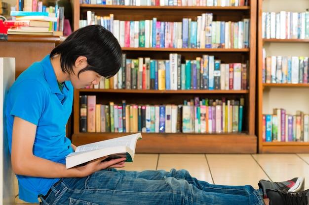 Studente nel libro di lettura della biblioteca