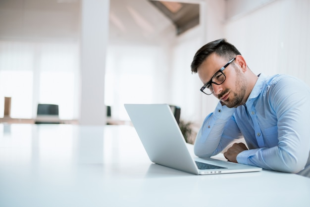 Studente o uomo d'affari stanco che lavora con il computer portatile nell'ufficio