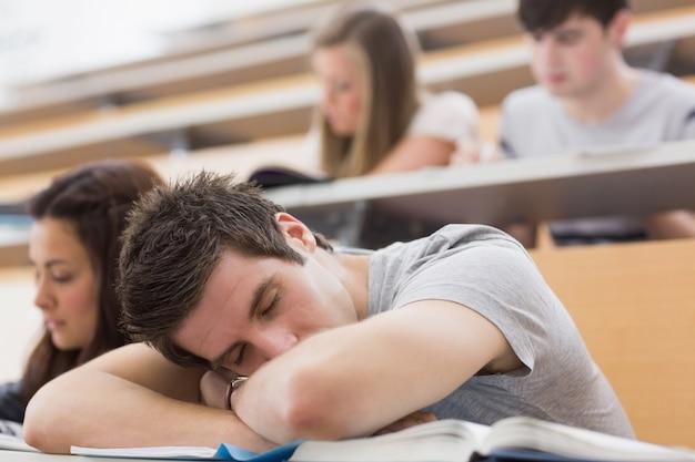 Studente seduto in aula e dormire