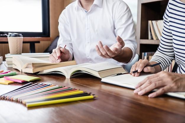 Studente seduto in biblioteca, studiando e leggendo, facendo i compiti e le lezioni di pratica preparazione esame