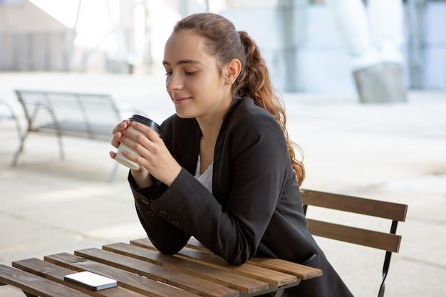 Studente sereno sorridente che gode dell'intervallo per il caffè