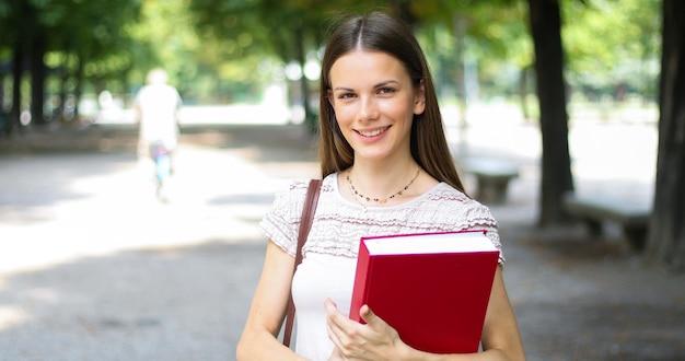 Studente sorridente all'aperto che tiene un libro