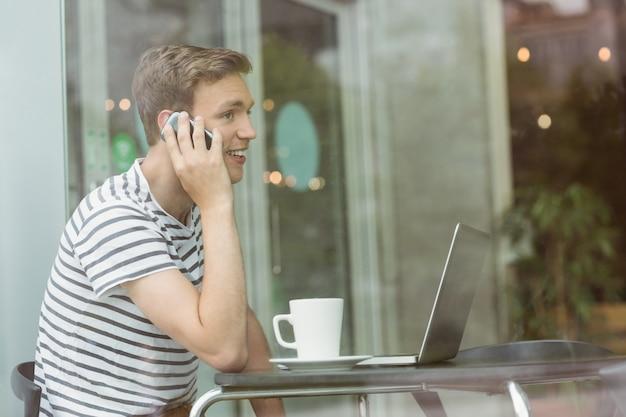Studente sorridente che utilizza computer portatile e smartphone in caffè