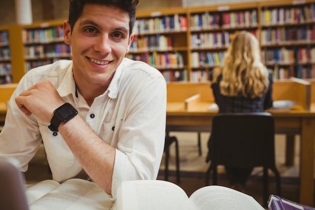 Studente sorridente che utilizza il suo computer portatile mentre lavorando nella biblioteca