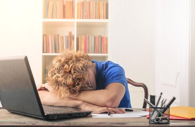 Studente stanco che dorme sulla sua scrivania