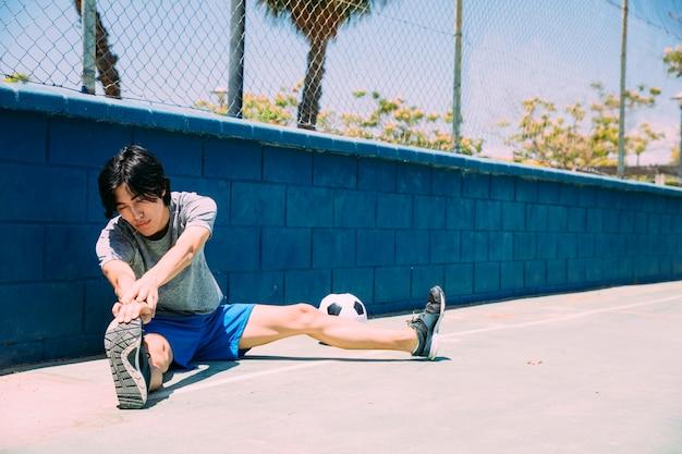Studente teenager asiatico serio che riscalda le gambe