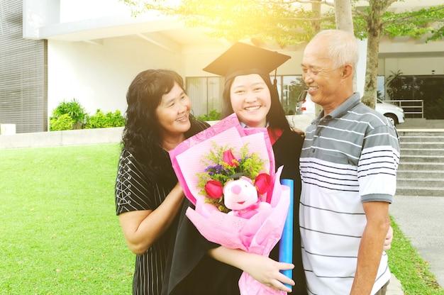 Studente universitario asiatico e famiglia festeggia la laurea all'aperto