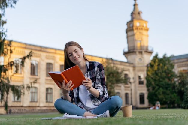 Studente universitario che studia, legge un libro, impara la lingua, preparazione all'esame, sedendosi sull'erba, concetto di istruzione