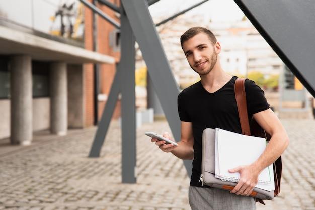 Studente universitario che tiene i suoi appunti e telefono