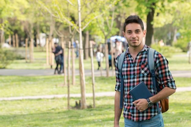 Studente universitario con libro all'aperto