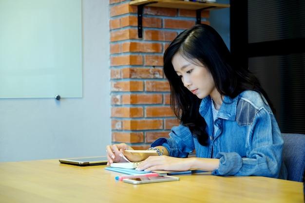 Studente universitario della donna asiatica nello studio casuale sul taccuino di carta