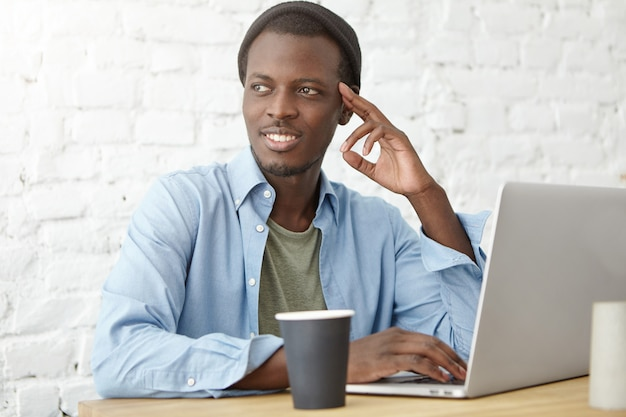 Studente universitario sylish african american che mangia caffè durante il pranzo in mensa, usando il portatile mentre si lavora sul progetto di diploma o si prepara per le lezioni. giovani pantaloni a vita bassa neri che godono della prima colazione al caffè