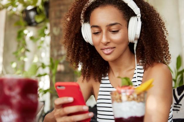 Studentessa afroamericana ascolta lezione audio in cuffie moderne su smart phone, connessa a internet wireless in un accogliente bar, migliora la conoscenza della lingua straniera. tecnologia e gioventù