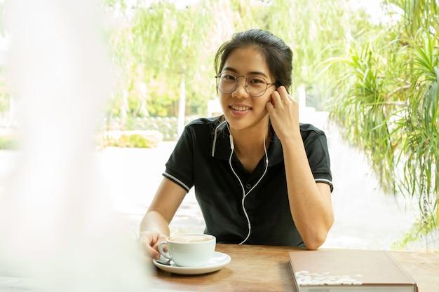 Studentessa asiatica che lavora al computer portatile con il trasduttore auricolare che esamina macchina fotografica.