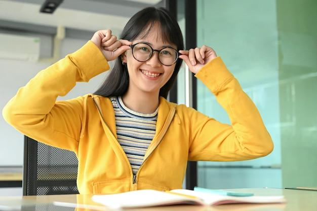 Studentessa asiatica con i vetri e sorrise per la macchina fotografica. sta leggendo libri di preparazione agli esami.