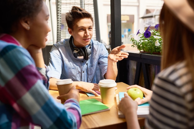 Studentessa asiatica talking to friends in cafe
