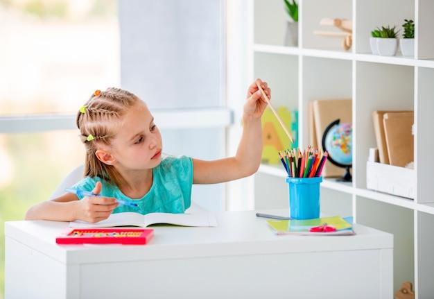 Studentessa carina con i capelli intrecciati alla scrivania