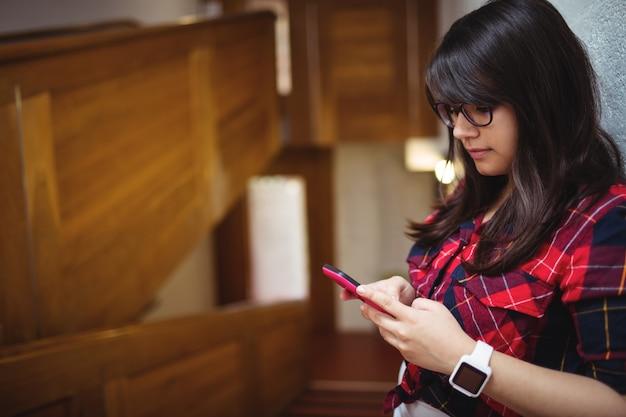 Studentessa che per mezzo del telefono cellulare