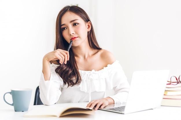 Studentessa che si siede e che studia e che impara online con il computer portatile e che legge un libro prima dell'esame a casa. concetto di educazione