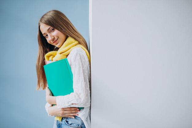 Studentessa che sta con le cartelle variopinte