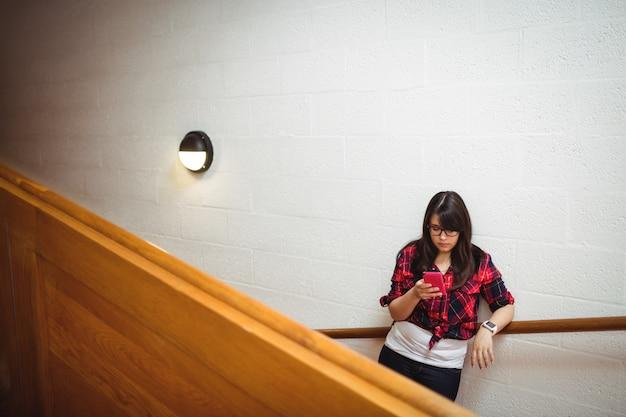 Studentessa che sta sulla scala e che per mezzo del telefono cellulare