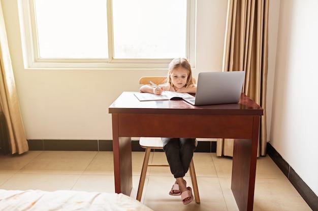 Studentessa che studia i compiti durante la sua lezione online a casa