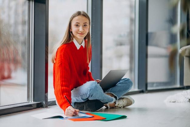 Studentessa che studia sul computer dalla finestra