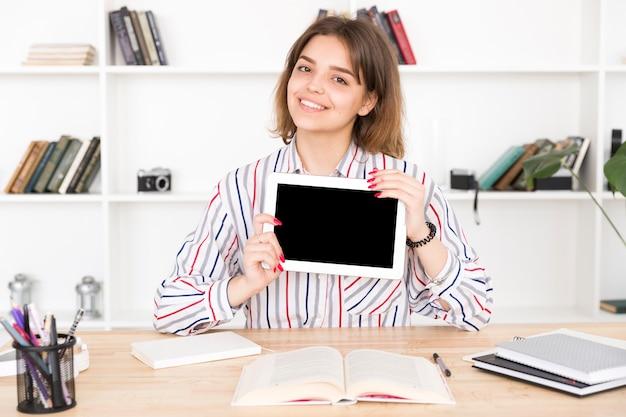 Studentessa che tiene compressa digitale in bianco