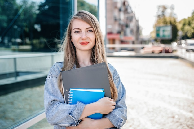 Studentessa che tiene una cartella del taccuino nelle sue mani e in piedi sulla strada