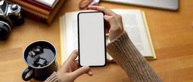 Studentessa che usando derisione sullo smartphone sulla tavola di studio con i libri e la tazza di caffè