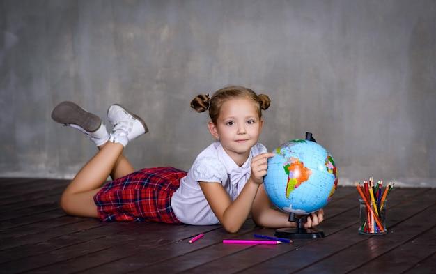 Studentessa con colori e globo terrestre. concetto di scuola