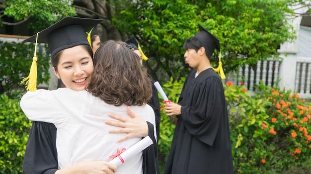 Studentessa con gli abiti di laurea e cappello abbraccia il genitore nella cerimonia di congratulazioni.