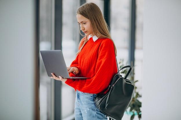 Studentessa con il computer portatile che fa una pausa la finestra in corridoio