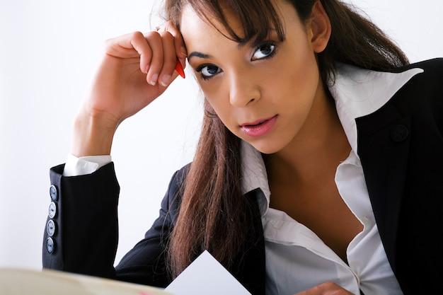 Studentessa con libri aperti, guardando lo spettatore
