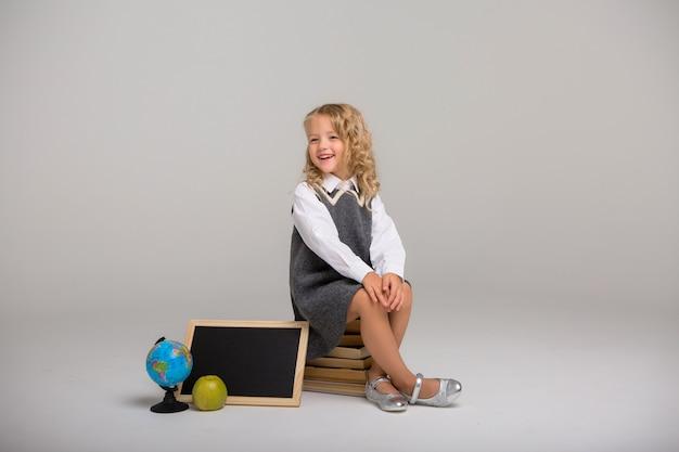 Studentessa con libri su uno sfondo chiaro