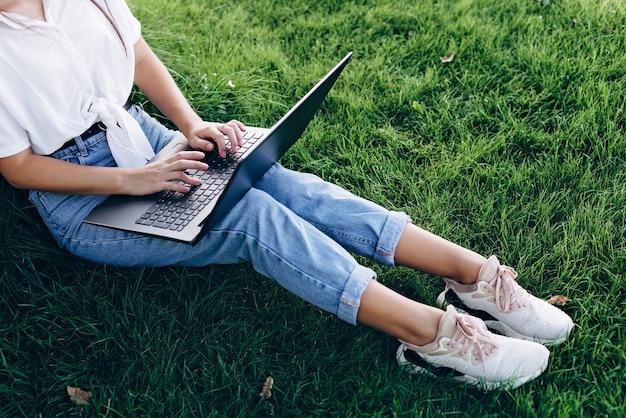 Studentessa con un laptop all'aperto si siede sull'erba nel parco