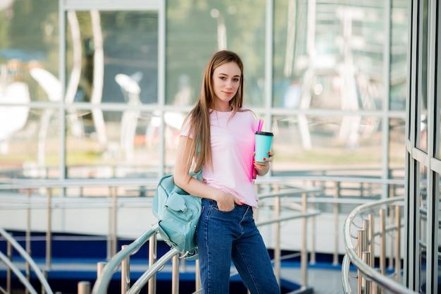 Studentessa con una tazza di caffè in strada
