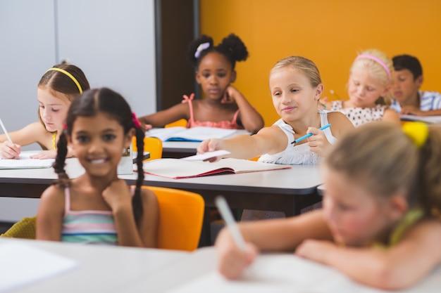 Studentessa dando chit ai suoi amici in classe