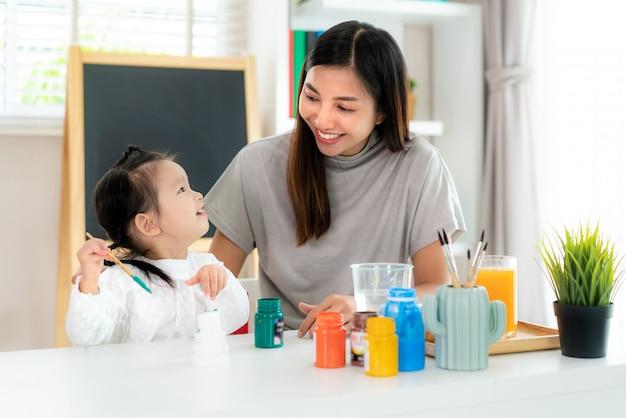 Studentessa dell'asilo asiatica con la madre che dipinge bambola di gesso con vernice acrilica di colore di acqua in salotto a casa. homeschooling e apprendimento a distanza.