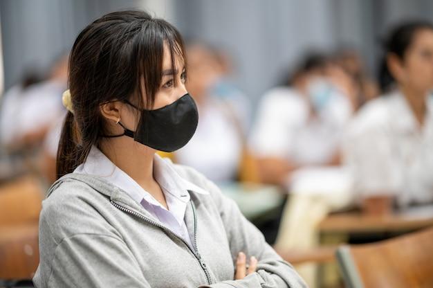 Studentessa di college femminile che indossa una maschera in una classe all'università