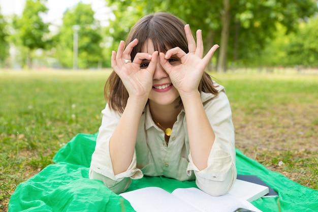 Studentessa di college spensierata felice che fa smorfie per la macchina fotografica