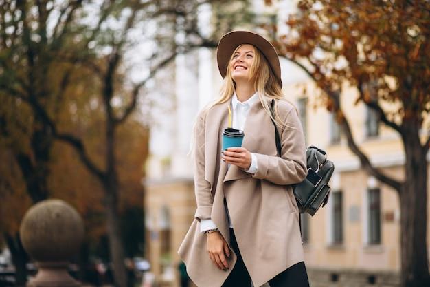 Studentessa in cappello che beve caffè