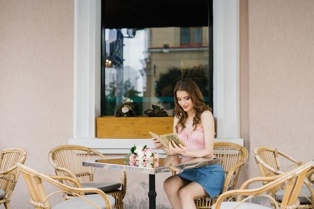 Studentessa in modo romantico, leggendo un libro a un tavolo in un caffè di strada